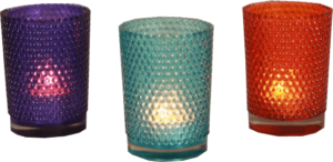Collection of candles in colourful candle holders